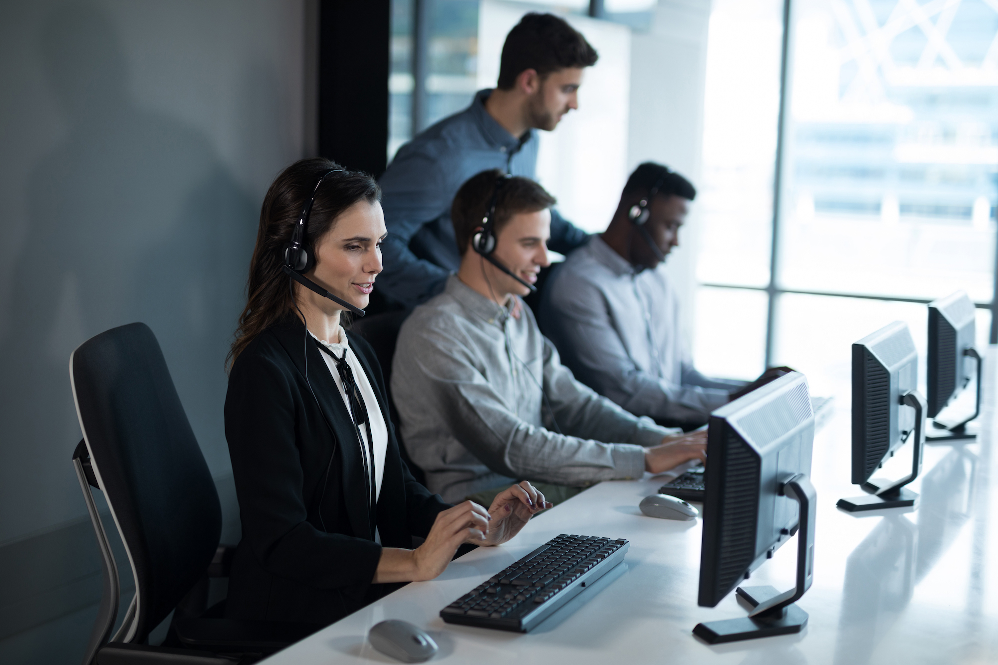 Customer service executive trainer monitoring her team in office